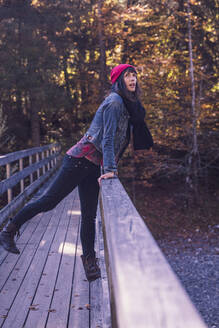 Woman wearing red woolly hat and denim jacket on a bridge in autumn - DHEF00036