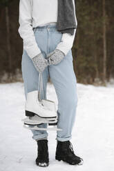 Crop view of woman with ice skates in winter - EYAF00810