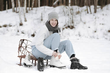 Portrait of smiling woman putting on ice skates on snow field - EYAF00813