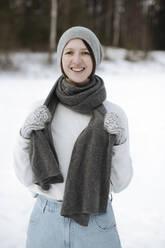 Portrait of happy woman standing on a snow field - EYAF00816