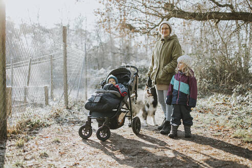 Mother with children and border collie during forest walk in autumn - DWF00531