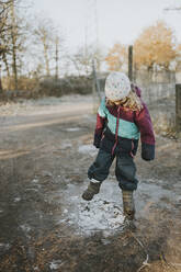 Girl kicking on frozen puddle - DWF00534