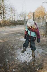 Girl kicking on frozen puddle - DWF00534