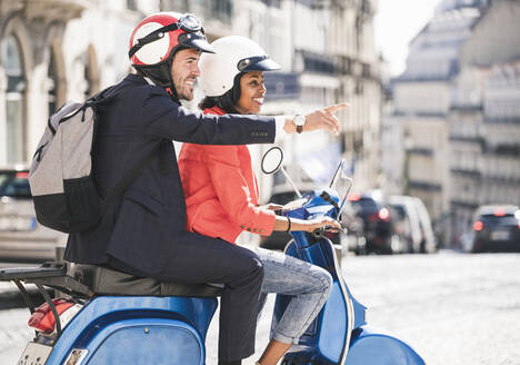 Happy young business couple riding motor scooter in the city, Lisbon, Portugal - UUF20118