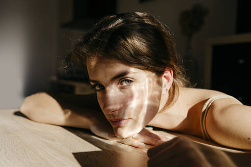 Portrait of young woman leaning on wooden table at sunlight - TCEF00037