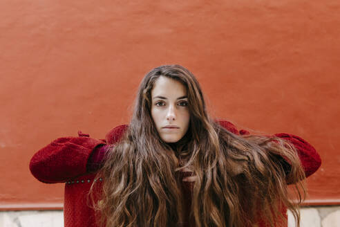 Portrait of selfconfident young woman with long brown hair against red wall - TCEF00046