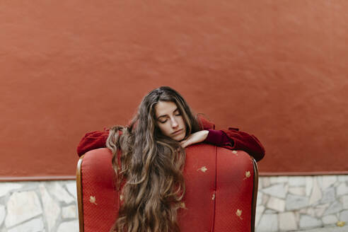 Portrait of young woman with long brown hair leaning on back rest of red lounge chair - TCEF00049