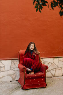 Portrait of young woman with long brown hair crouching on red lounge chair - TCEF00052