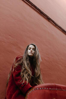 Portrait of young woman with long brown hair against red wall - TCEF00055