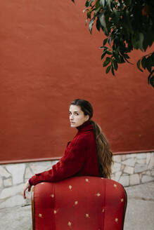 Portrait of young woman wearing red coat leaning on lounge chair - TCEF00058