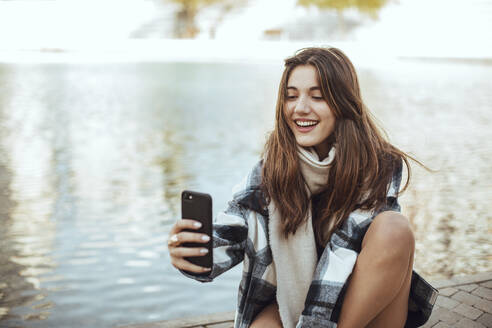 Young brunette woman using smartphone and taking a selfie at lake - ACPF00659
