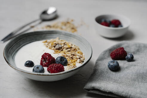 Bowl of granola with yogurt, blueberries and raspberries - JMHMF00039