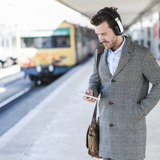 Young businessman with cell phone and headphones at the train station - UUF20147