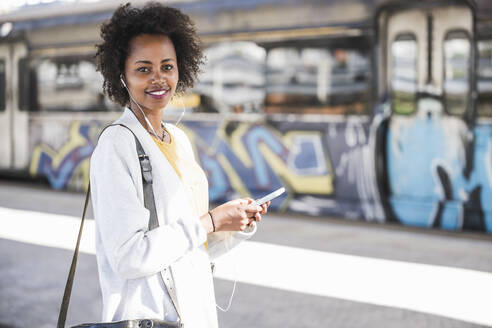 Portrait of smiling young woman with cell phone and earphones at the train station - UUF20162