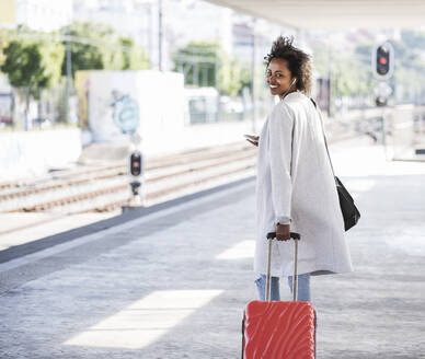 Smiling young woman with rolling suitcase at the train station - UUF20168