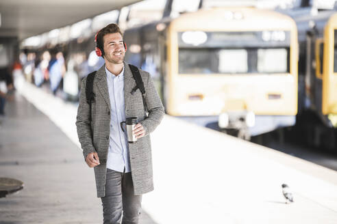 Young businessman with coffee mug and headphones at the train station - UUF20171