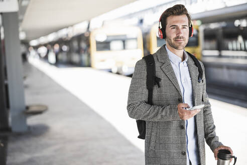 Young businessman with cell phone and headphones at the train station - UUF20174