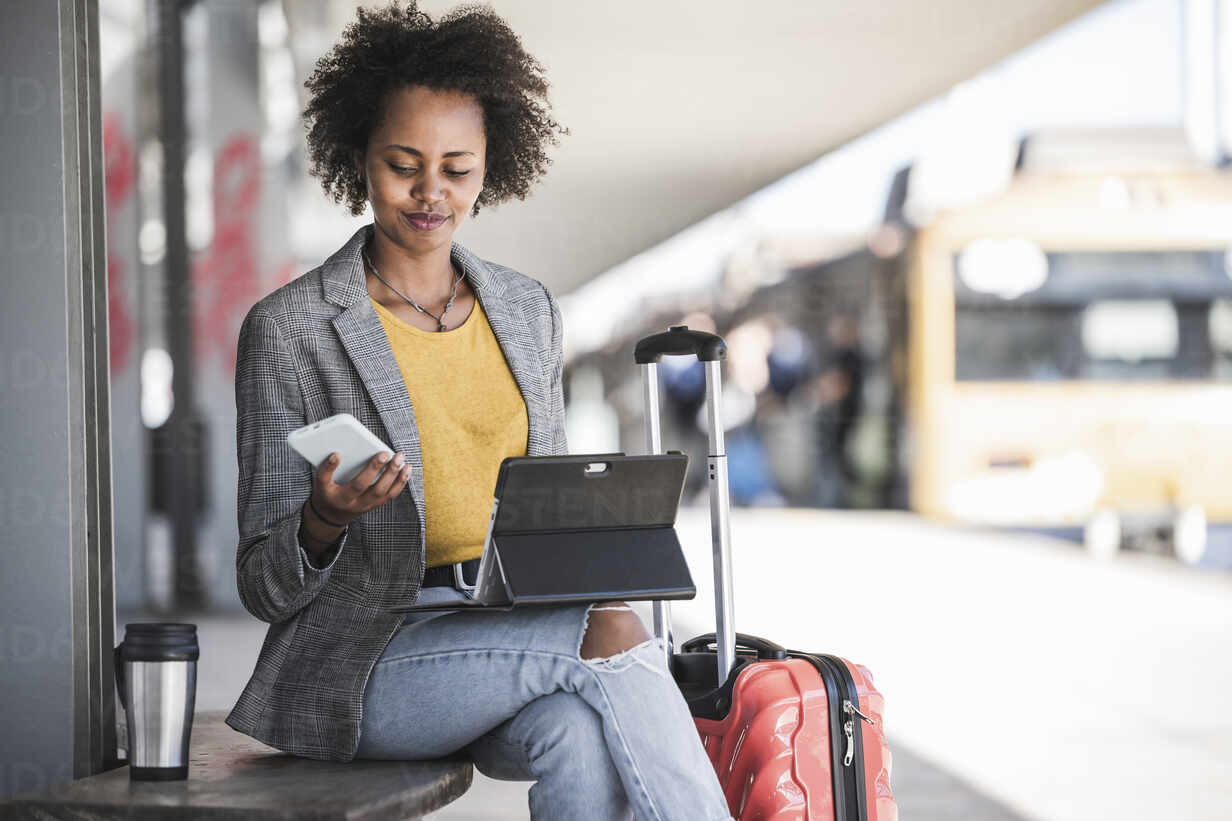 Young businesswoman using tablet and smartphone at the train station - UUF20177 - Uwe Umstätter/Westend61