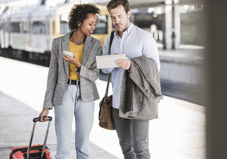 Young businessman and businesswoman using tablet together at the train station - UUF20189