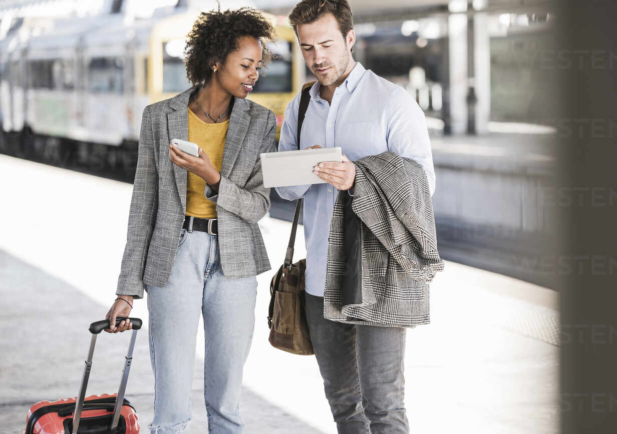 Young businessman and businesswoman using tablet together at the train station - UUF20189 - Uwe Umstätter/Westend61