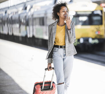 Happy young woman using cell phone at the train station - UUF20192