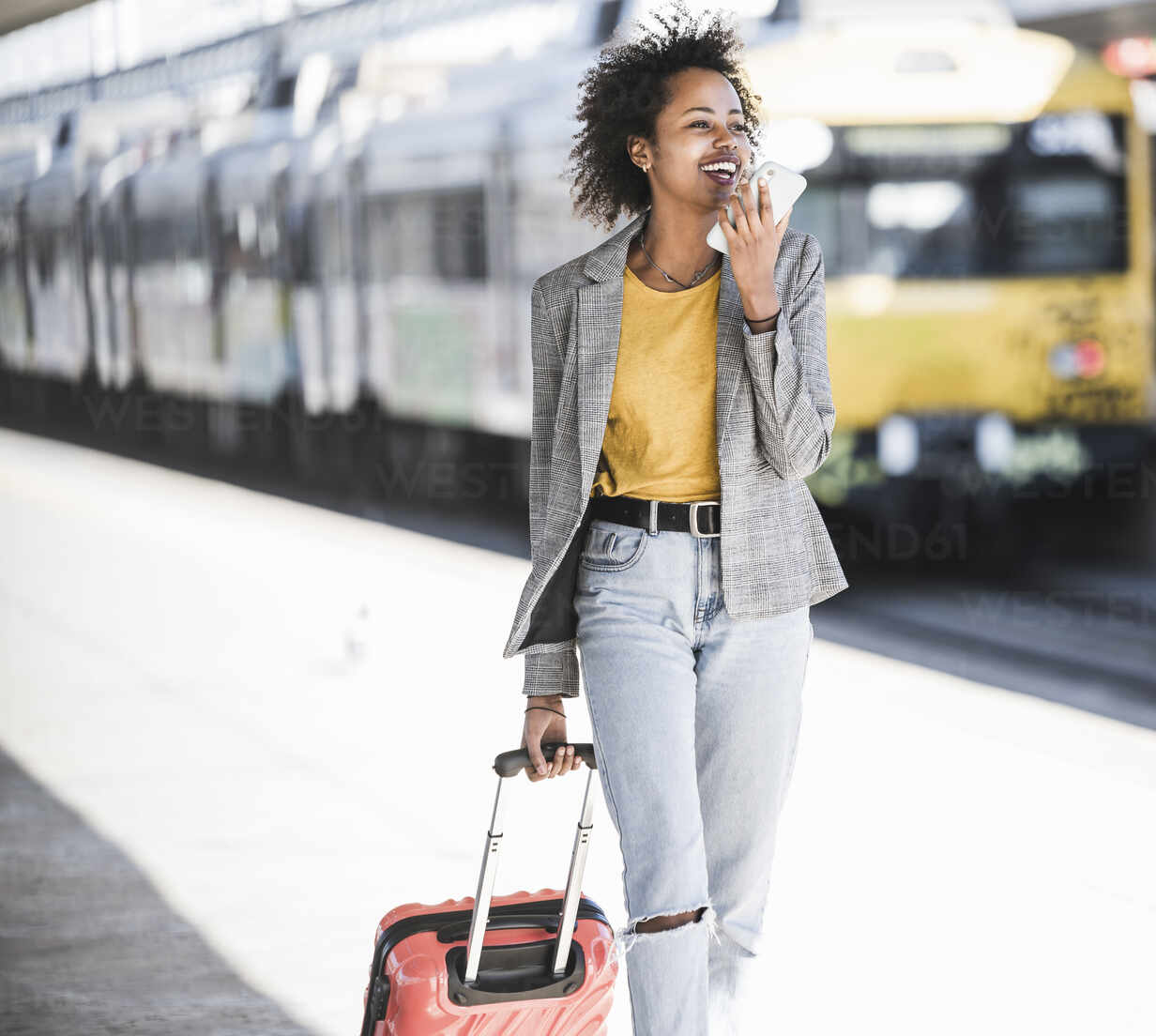Happy young woman using cell phone at the train station - UUF20192 - Uwe Umstätter/Westend61