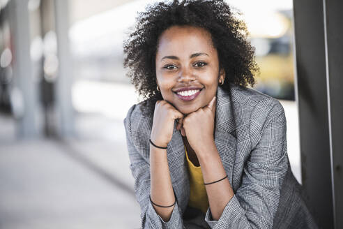 Portrait of smiling young businesswoman at the train station - UUF20204