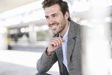 Portrait of smiling young businessman at the train station - UUF20210