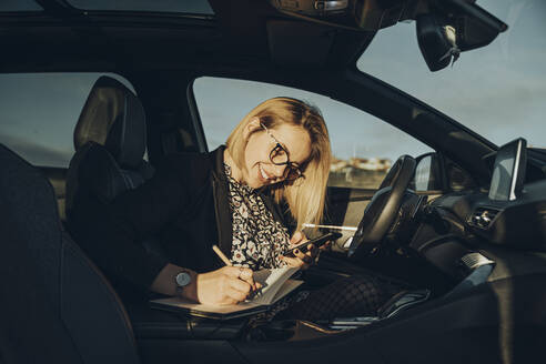 Young blond woman using smartphone in the car, writing in a notebook - MTBF00309