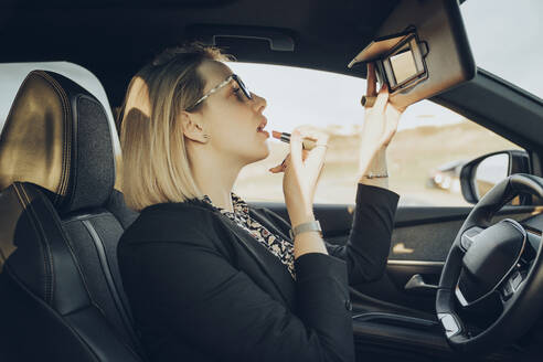 Young blond businesswoman in a car applying lipstick - MTBF00315