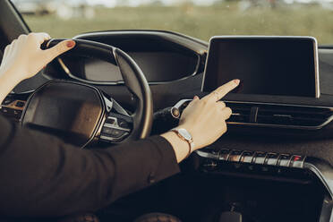 Young woman using navigation device in car - MTBF00318