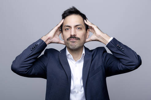 Portrait of businessman with hands on head - FLLF00379
