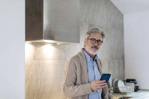 Portrait of mature man with cell phone in kitchen at home - SODF00550