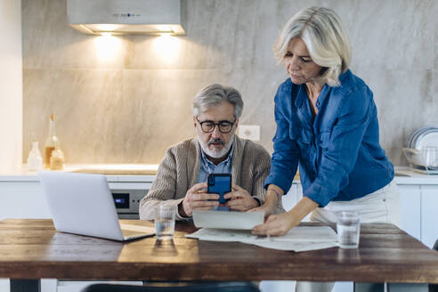 Mature couple with papers, cell phone and laptop on kitchen table at home - SODF00562
