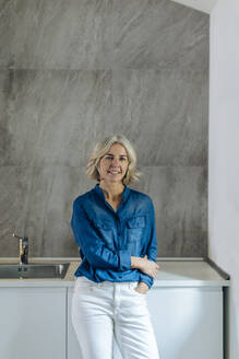 Portrait of smiling mature woman in kitchen at home - SODF00580