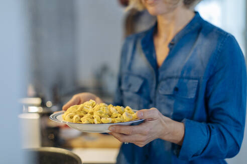 Close-up of woman holding a plate with tortellini in kitchen at home - SODF00604
