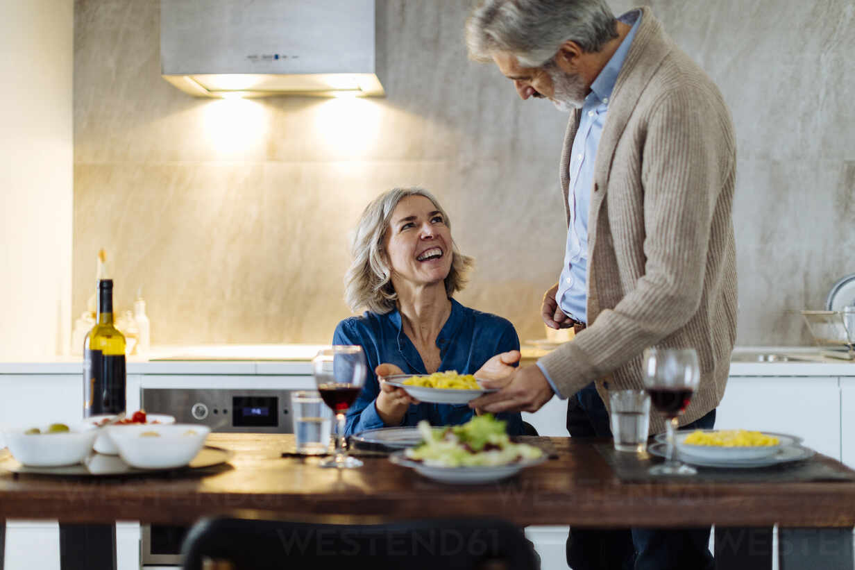 Mature man serving dinner to happy wife in kitchen at home - SODF00616 - Sofie Delauw/Westend61