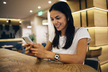 Black-haired woman using smartphone in cafe - OYF00099