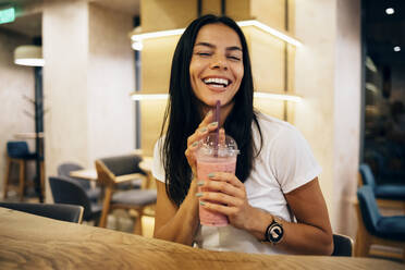 Black-haired woman drinking a smoothie in cafe - OYF00108