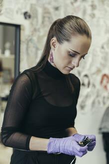 Female tattooist prepairing her tattoo machine - MTBF00329