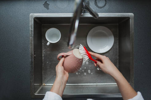 Woman washing up mug - JOHF05310