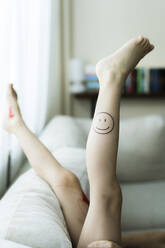 Girl's leg with painted smiley face - PSIF00362