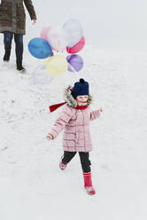 Little girl with ballons running down a hill in winter - PSIF00371