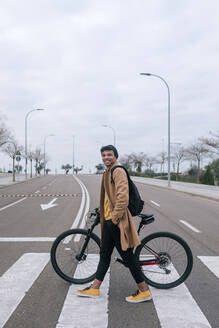 Young man with bicycle crossing a street in the city - GRCF00084