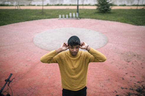 Portrait of confident young man outdoors putting on beanie - GRCF00093