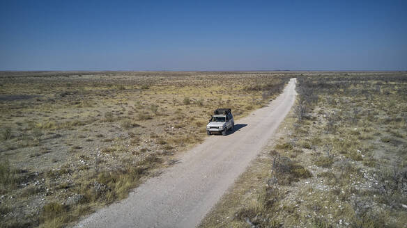 Aerial view of a white jeep on a dirt track, Damaraland area, Namibia - VEGF01415
