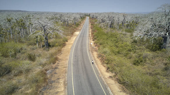 Aerial view of a woman at a road hitchhiking, Cabo Ledo area, Angola - VEGF01447