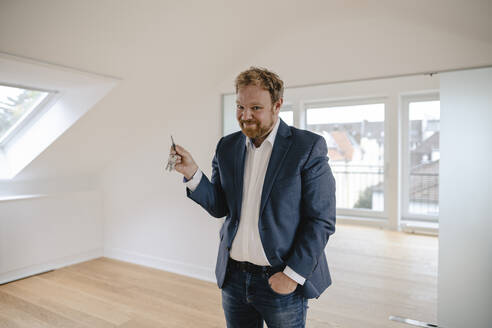 Portrait of smiling businessman standing in empty apartement holding key - GUSF03182