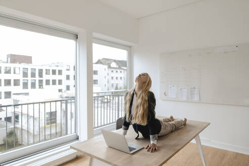 Young businesswoman practicing yoga on desk in office - GUSF03191