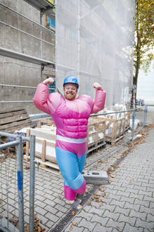 Portrait of a proud man wearing pink bodybuilder costume and hard hat at construction site - GUSF03227
